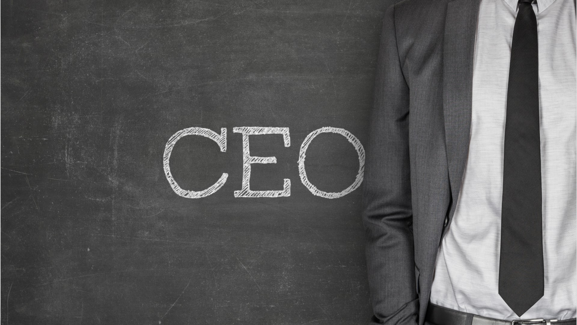torso of person wearing a suit jacket and tie, standing in front of C E O written on a chalkboard