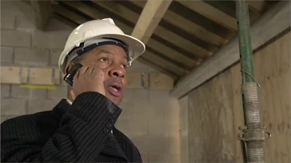 man wearing a suite and hard hat in a building construction site talking on a phone