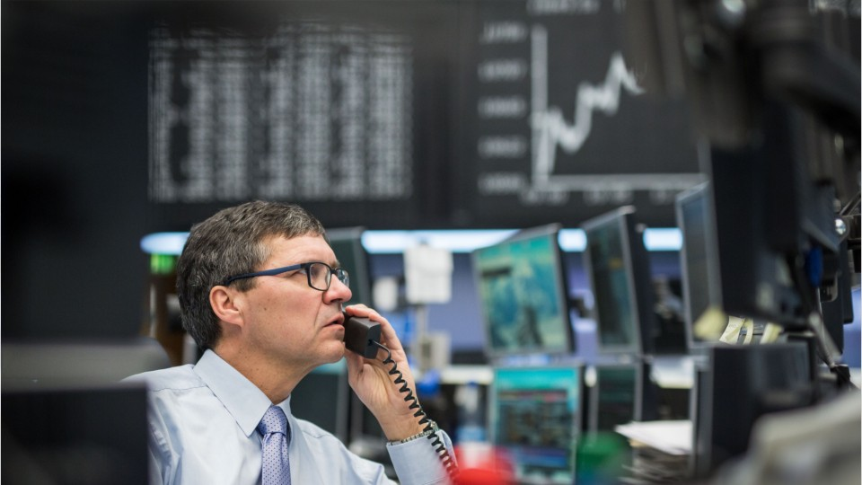 person on a phone looking at stock market computer screen