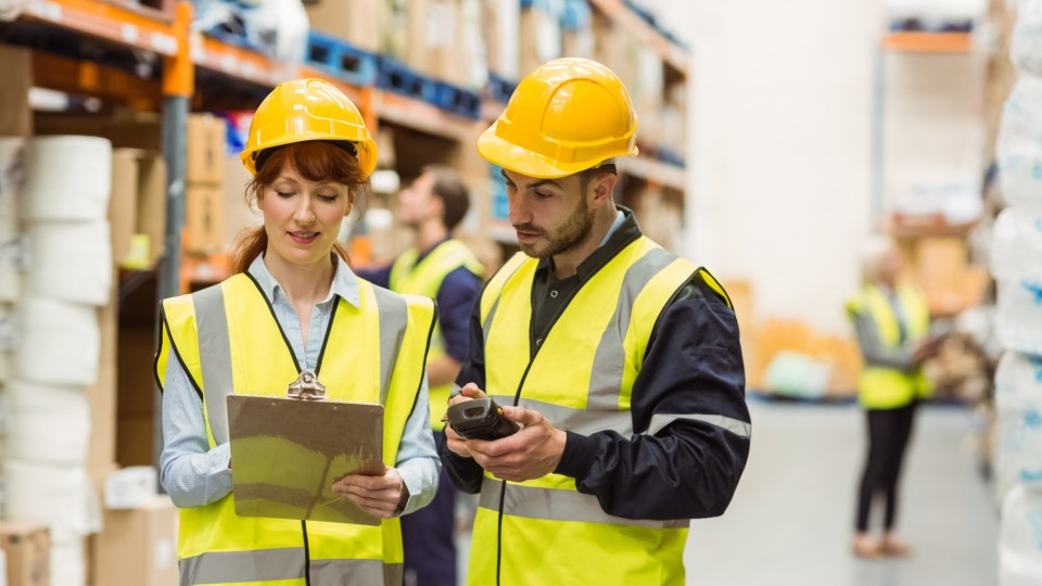 two people standing in a warehouse reviewing paperwork