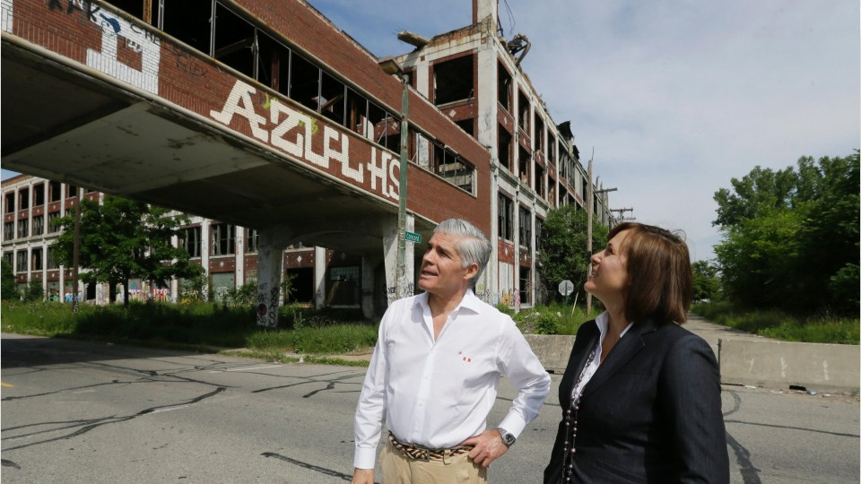 two people standing outside an abandoned factory building