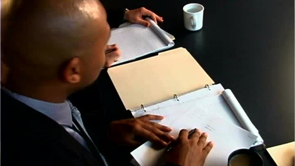 person in a suit at a conference table writing on a notepad