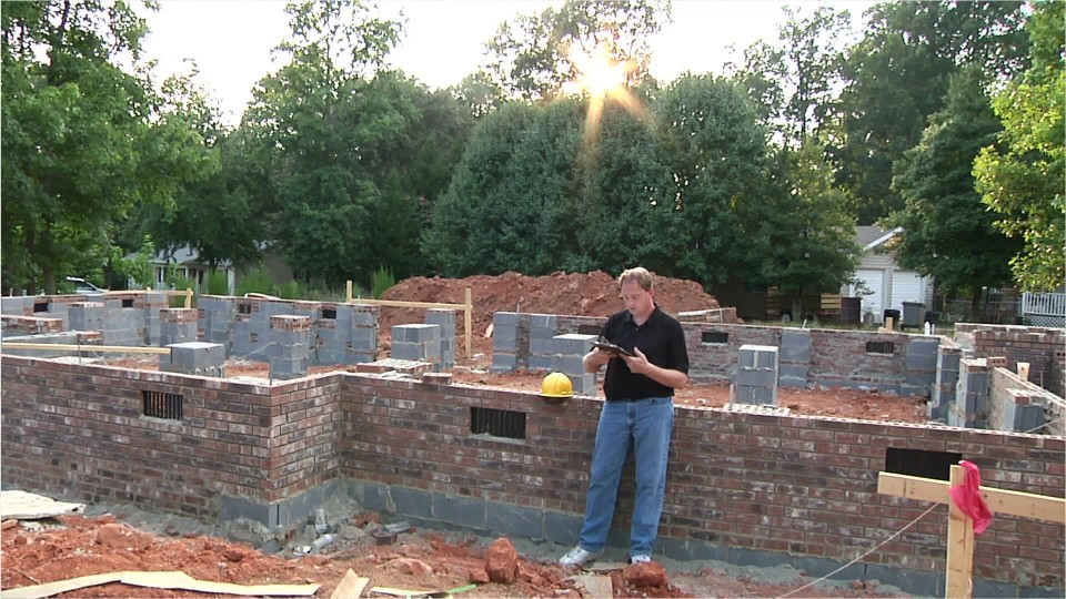 appraiser standing next to the foundation of a new home