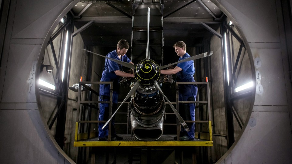 two people working on an airplane engine
