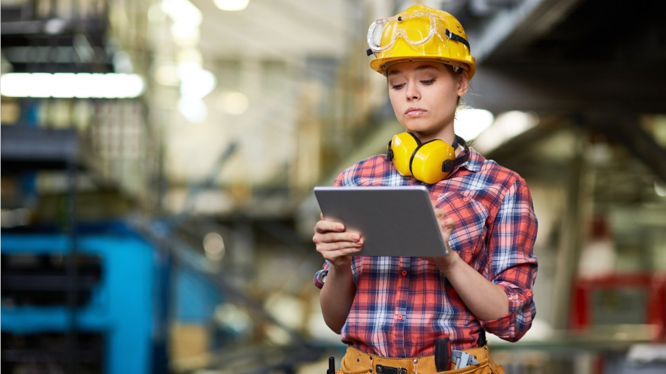 woman holding a tablet and wearing a hard hat in a factory