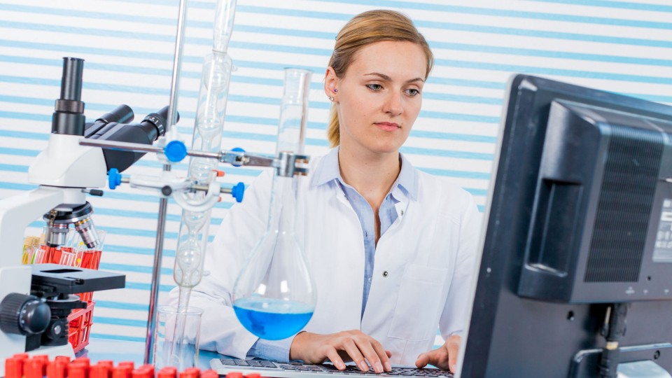 person wearing a lab coat typing on a computer next to a microsocpe and beakers