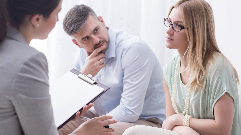 man and woman talking with a therapist