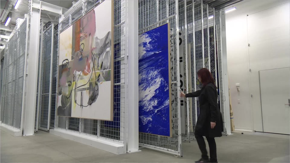 woman pulling a wall-sized painting out of vertical storage archive