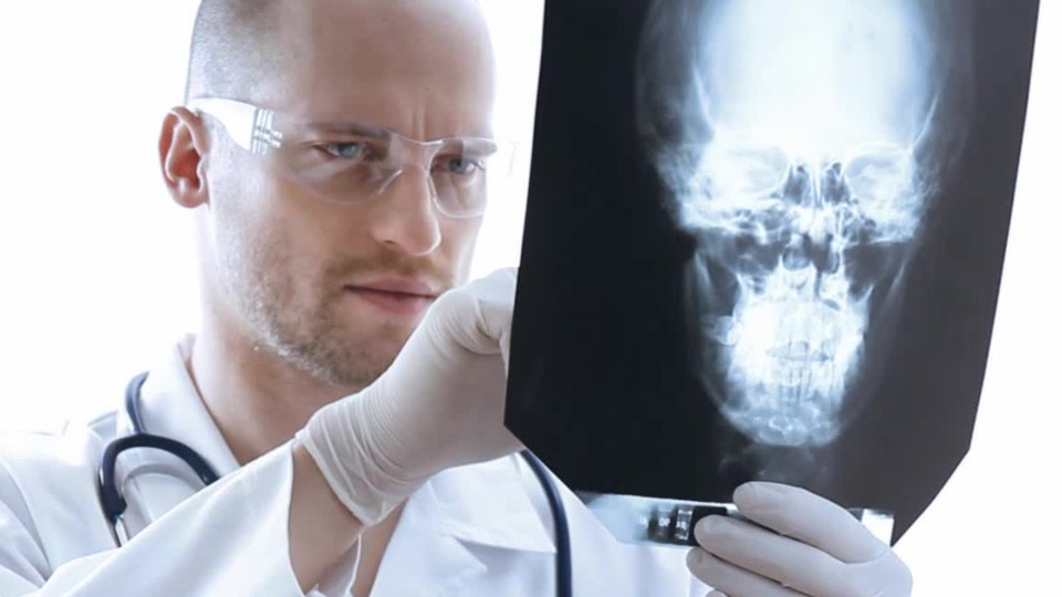 person in doctors coat wearing a stethoscope looking at a facial x-ray