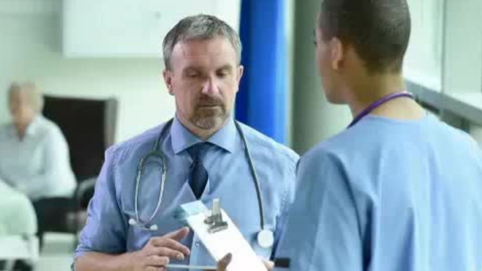 person with stethoscope talking to another person in scrubs holding a clipboard