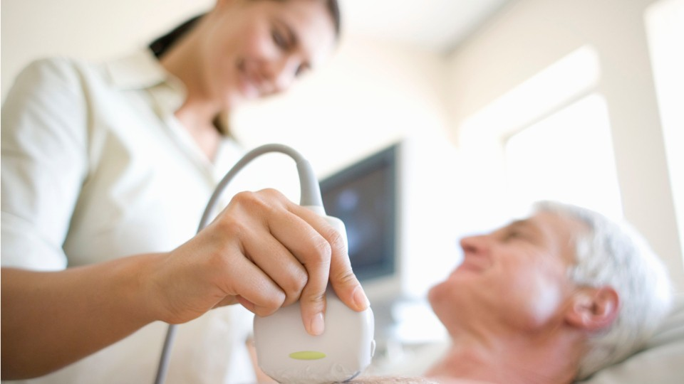 person doing an ultrasound on a patients chest