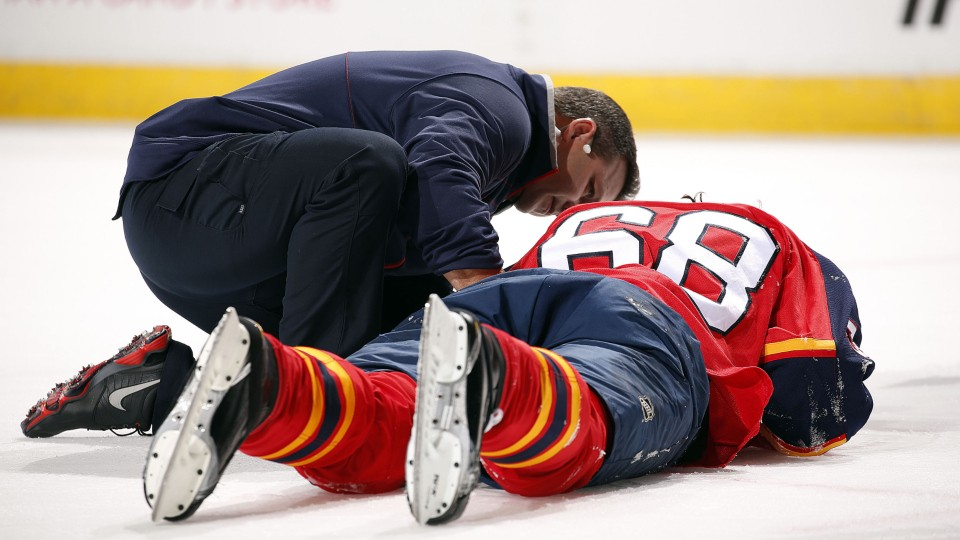 person helping a hockey player who is face down on the ice