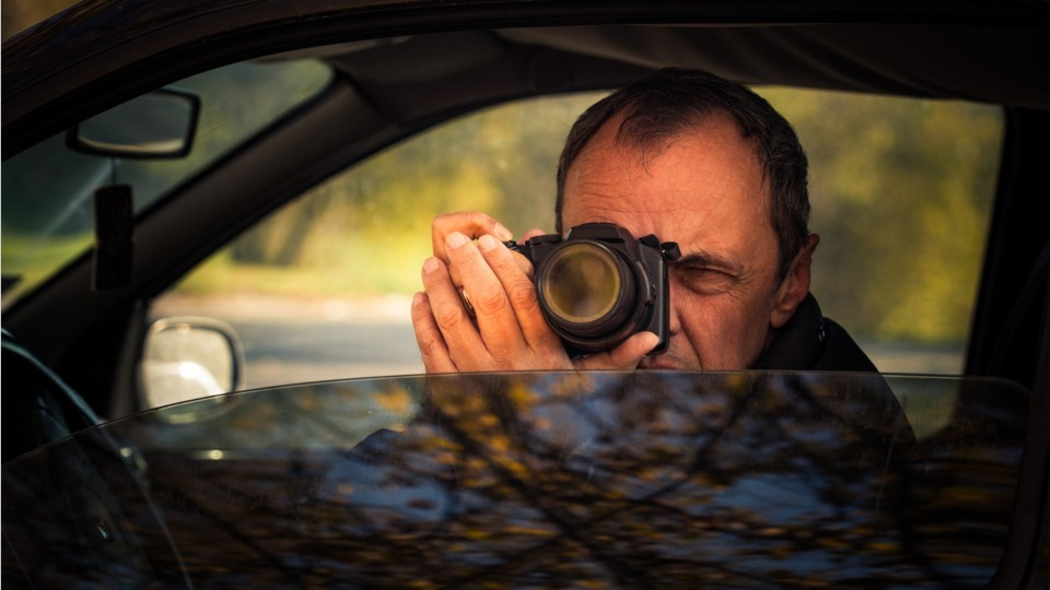 person sitting in a car taking pictures with a camera and zoom lens
