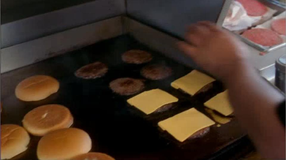 hamburgers cooking on restaurant griddle