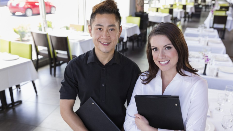 host and hostess holding menus in a restaurant