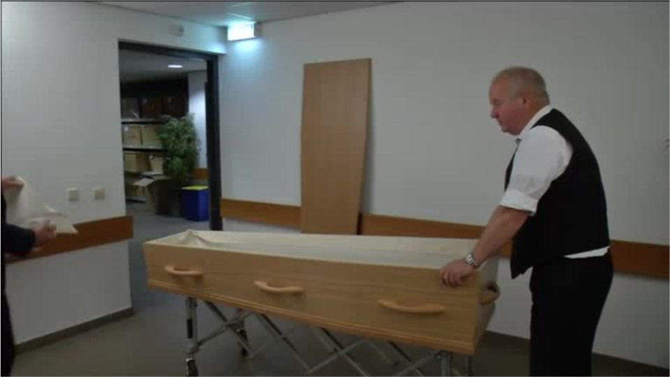 person rolling a casket into a funeral home