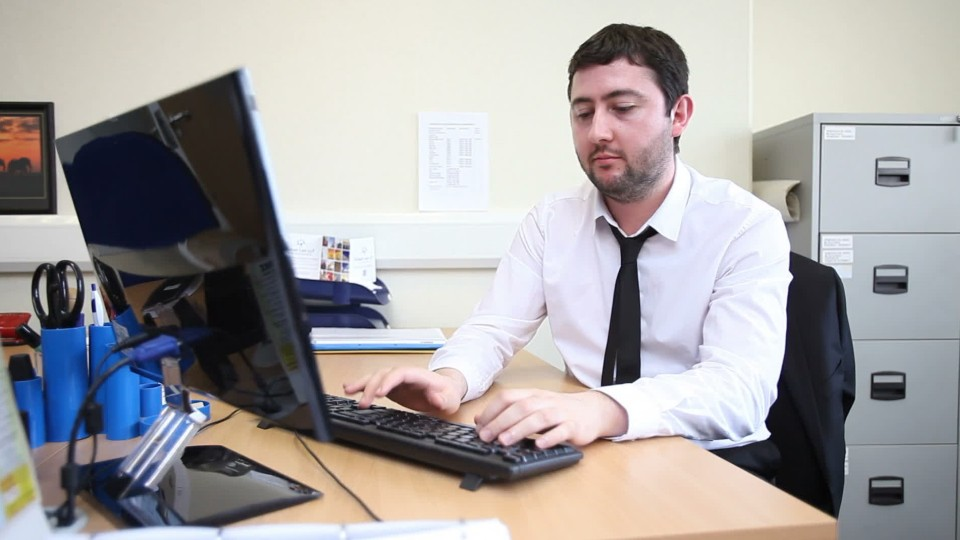person sitting at a desk typing on a computer keyboard