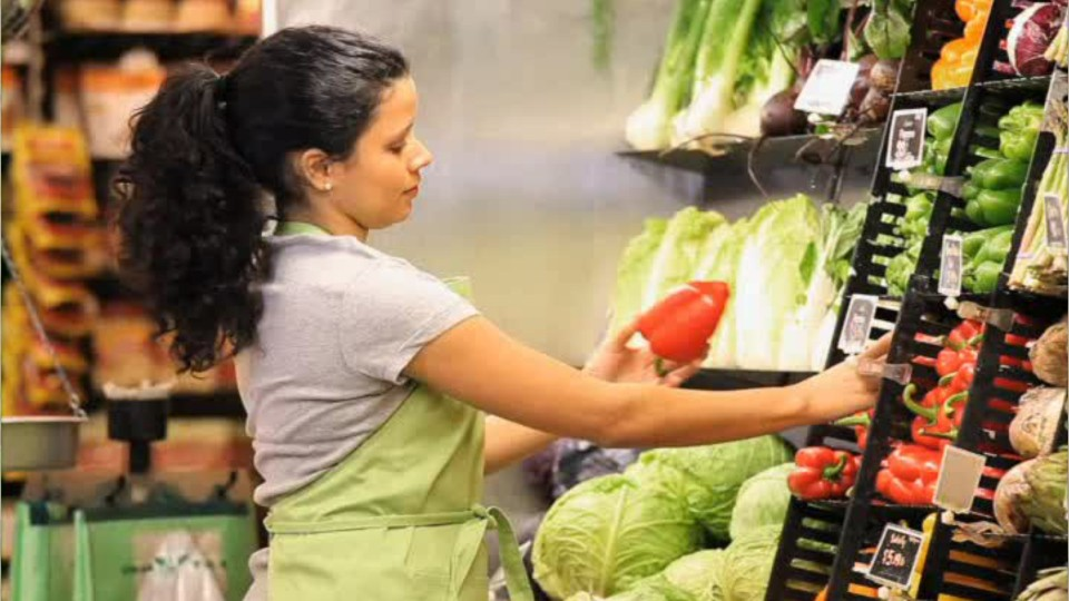 grocery store employee restocking shelves with fresh vegetables