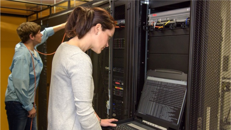 woman working on a server room computer work station