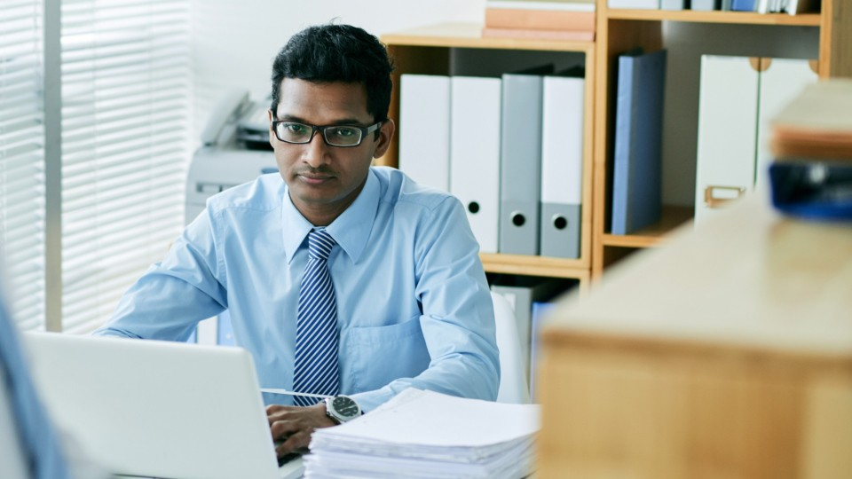 person in dress shirt at tie working on a computer