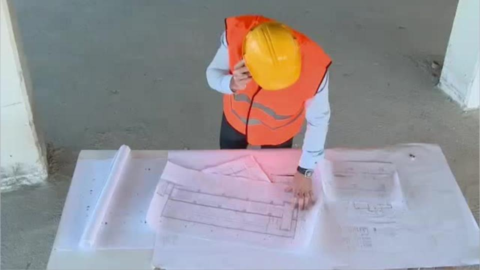 construction supervisor wearing a hard hat and orange vest looking at plans on a job-site table