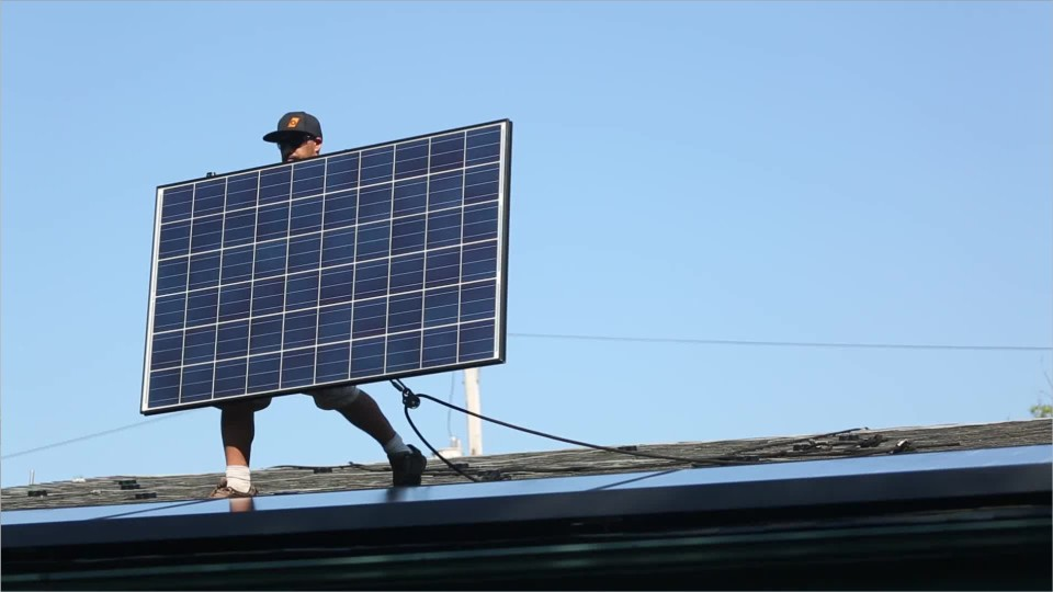 person walking on a roof carrying a solar panel