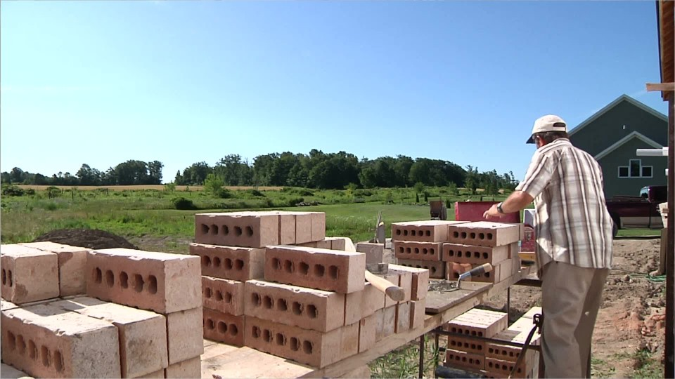 person stacking bricks outside at a construction site