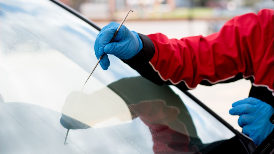 person repairing a chip in a car windshield