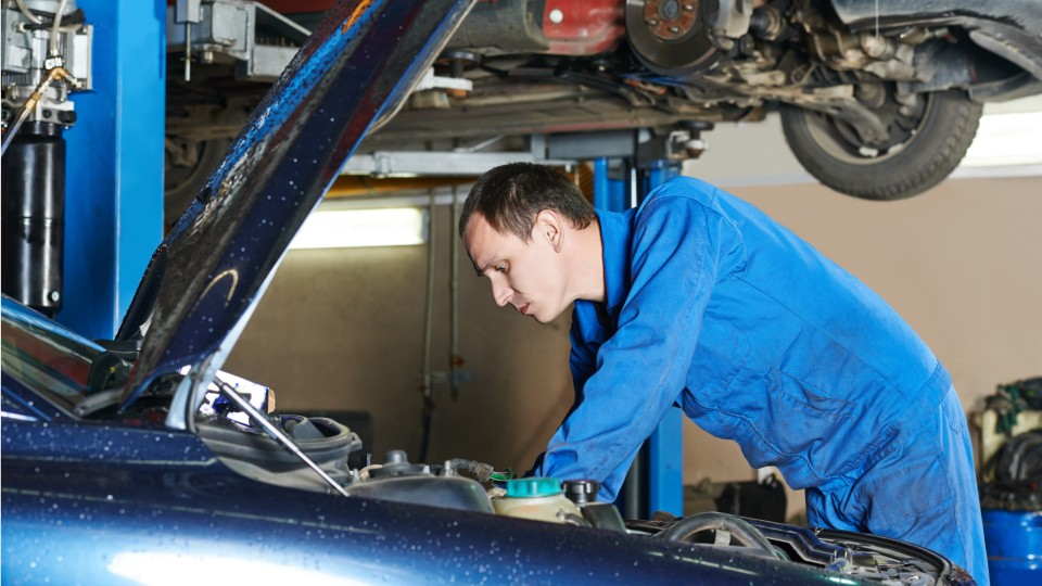 auto mechanic looking under the hood of a car in a repair shop