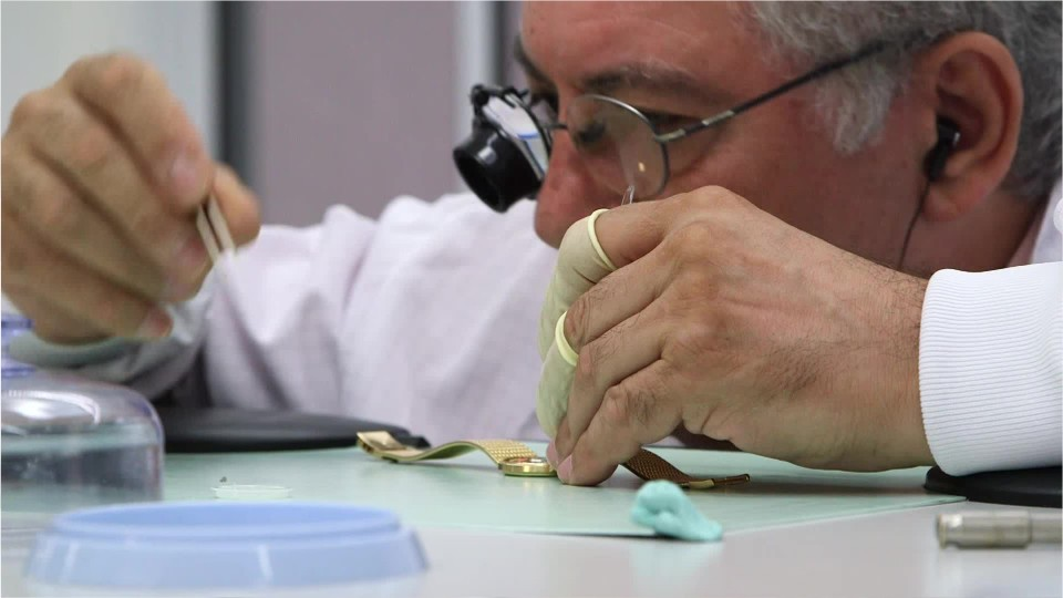 watch repairer fixing a watch at a work table