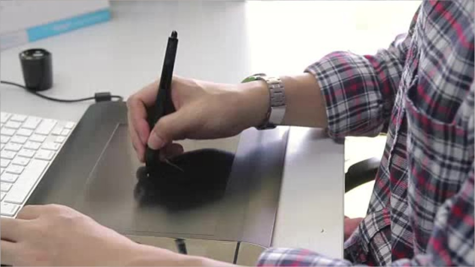 person using a digital drawing pad and stylus in front of a computer