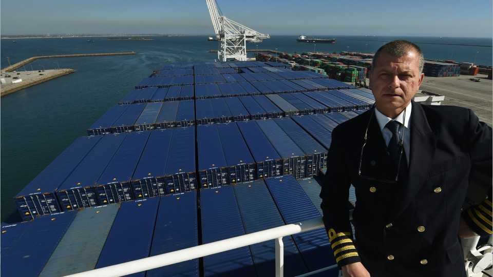 captain standing on the bridge of a fully loaded cargo ship