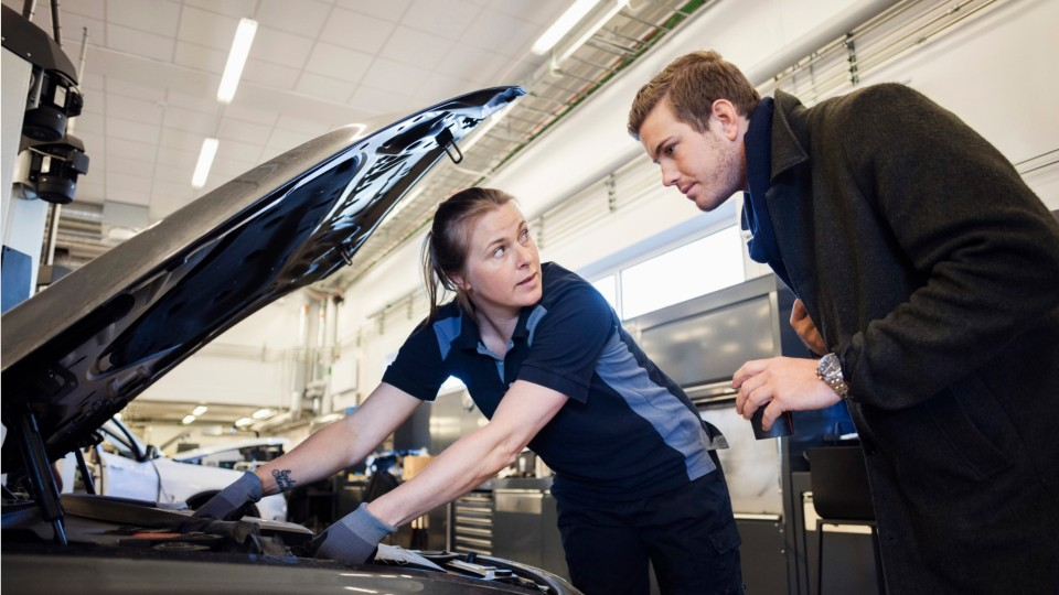 two people looking under the hood of a car